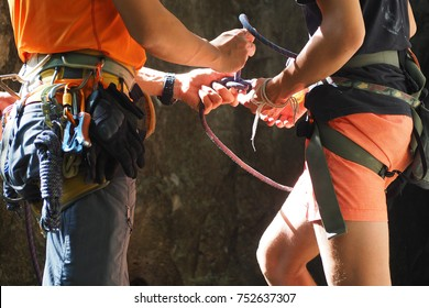 Rock climbing instructor is coaching how to tie knot