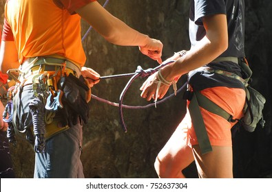 Rock climbing instructor is teaching how to tie the figure eight knot