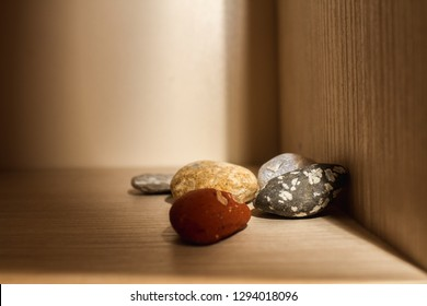 A rock collection on a wooden shelf.