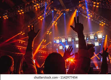 Rock concert, people with raised up hands dancing and enjoying loud music, having fun in night club, with pleasure spending time on musicl festival