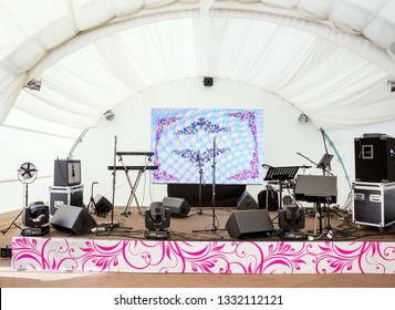 Rock concert stage with musical instruments prepared for the musicians before the performance in the closed summer hall under the tent