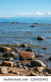 rock covered beach in countryside in Latvia, large rocks in water with calm wind and sunshine