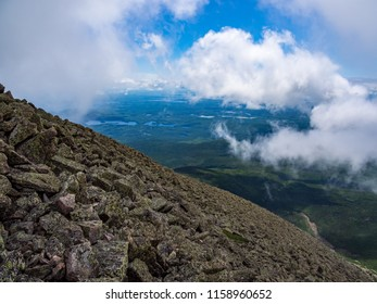 Rock covered slope of a mountain, low clouds, expansive valley view below.  Along Knife's Edge of Katahdin, Baxter State Park, Maine.