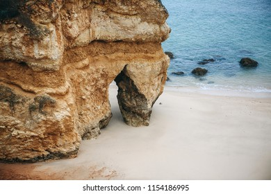 A rock with a crevice on the beach in the city called Lagos in Portugal. Near the Atlantic Ocean.