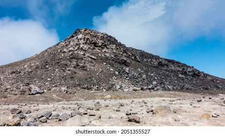 A rock devoid of vegetation, against a background of blue sky and clouds. Volcanic  stones are scattered on the slopes and at the base. Kamchatka.