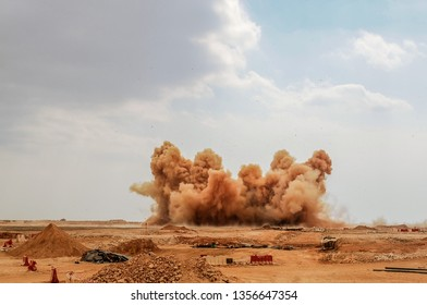 Rock dust clouds after the powerful blast on the construction site in the desert of Oman