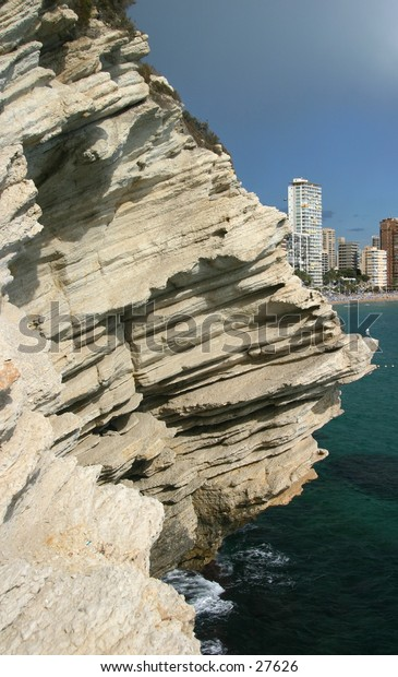 Rock face jutting out over sea with hotels and coastline in the background
