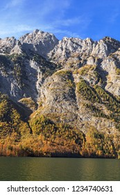Rock faces belonging to the Watzmann massif at the mountain lake Königssee in Bavaria, Germany. Berchtesgaden National Park. With mountain forest in autum foliage.