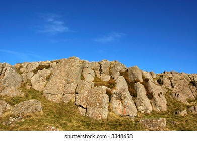 Rock feature and deep blue sky on summit of Dunmore, Scotland