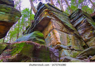 A rock formation next to a hiking trail with many 90 degree angles.