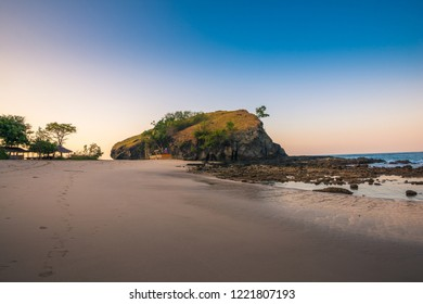 Rock formation on the beach at sunset and clear blue sky