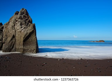 Rock formation on Praia Formosa beach - famous public black sand beach on Portuguese island of Madeira