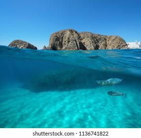 Rock formation on the sea shore with fish and sand underwater, split view above and below water surface, Mediterranean sea, La Isleta del Moro, Cabo de Gata-Níjar, Almeria, Andalusia, Spain