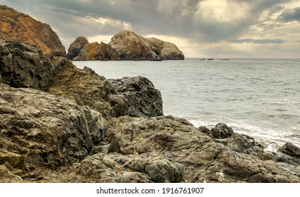 Rock formations against the backdrop of the ocean in the San Francisco Recreation Area, Rodeo Beach, California, USA. Seaside, beautiful landscape, California coast.
