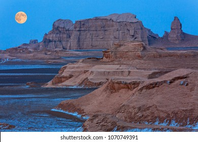 Rock formations known as Kalutes in the Lut Desert in Iran, with full moon rising.