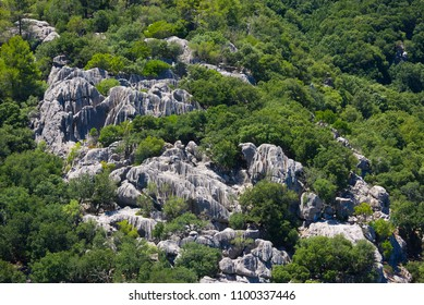Rock formations with vertical striations surrounded by vegetation on a hillside in Mallorca, Spain.