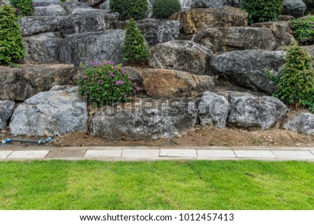 Rock Garden In The Park With Concrete Drain Cover And Green Lawn