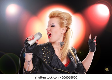 rock girl singer with microphone on color light background