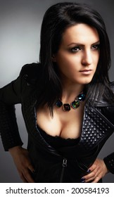 Rock girl, wearing leather jacket, sexy cleavage. Portrait on gray background.