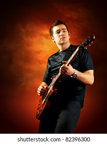 Rock guitarist play on the electric guitar, orange sky background