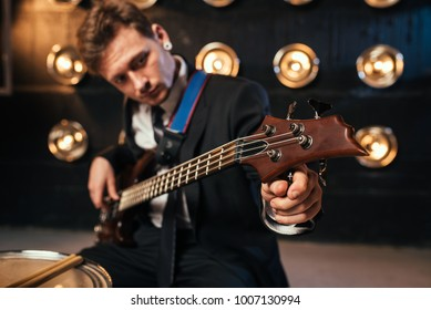 Rock guitarist in suit playing on bas-guitar