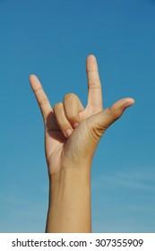 rock hand sign blue background