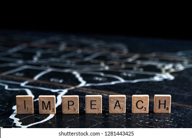 Rock Hill, SC/USA - 1/11/2019: Impeach spelled with Scrabble tiles on map of United States