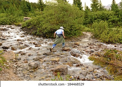 Rock Hopping across a Mountain Stream in the Canadian Rockies