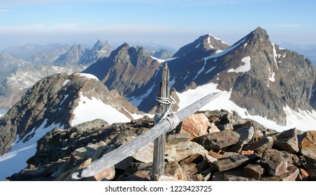 rock and ice and snow mountain landscape in the Swiss Alps in summer above Klosters in the Silvretta mountain range and a summit cross