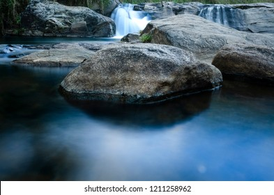 Rock in the middle of blue water in beautiful Brazilian waterfall