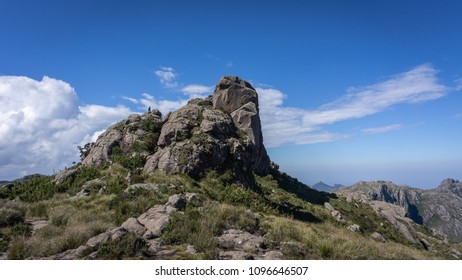 Rock mountain in Brazil, with a woman on top, creeping green nature and blue sky.