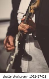 Rock music background, bass guitar player, closeup photo with soft selective focus