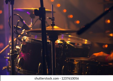 Rock music background, drummer plays with drumsticks on rock drum set. Warm toned close-up photo, soft selective focus