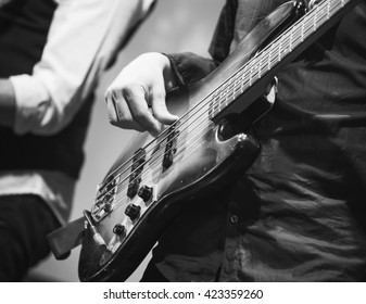 Rock music black and white background, bass guitar player, closeup photo with selective focus, selective focus