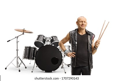 Rock music drummer holding a pair of drumsticks and posing with a drum set isolated on white background