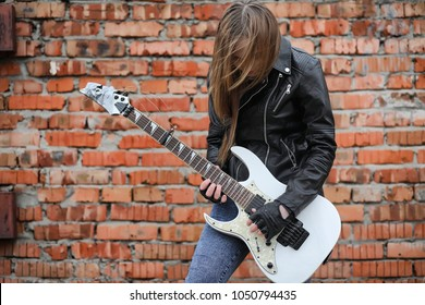 A rock musician girl in a leather jacket with guitar