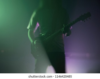 Rock musician playing the guitar in the spotlights in smoke. Punk.