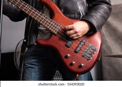 A Rock musician playing passionately bass in the rehearsal Studio.