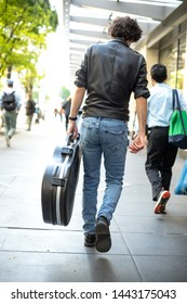 Rock musician wearing a leather jacket and carrying a guitar case on a city sidewalk, in a music busker concept