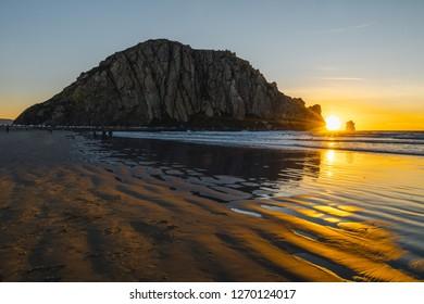 Rock in the ocean, Moro Rock in Moro Bay, California, beautiful sunset on the beach