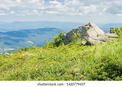 rock on the edge of a hill. sunny scenery in mountains. green grassy meadow and blue summer sky. idyllic landscape of carpathians