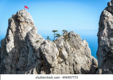Rock on Mount Ai-Petri with a red flag and trees against the sea in Crimea, Russia. Ai-Petri is one of the highest mountains in Crimea and tourist attraction. Scenic view of the rock range in summer.