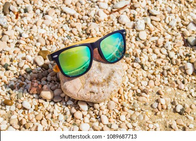 A rock with a pair of yellow glasses on it formulates a smile. Sumer holidays concept
