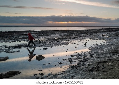A rock pool on a beach at sunset with reflections of the sky. A boy runs by with his reflection in the water