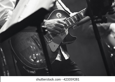 Rock and roll music background, guitar players on a stage, black and white, selective focus