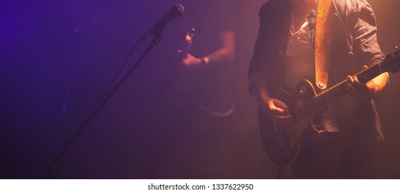 Rock and roll music panoramic background photo, guitar players on a stage, soft selective focus