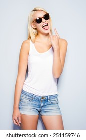 Rock and Roll queen. Beautiful young blond hair women making a face and gesturing while standing against grey background