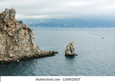 "Rock ""Sail"" near the city of Yalta. Crimea.  The ship sails to the sea. Overcast weather over the sea."