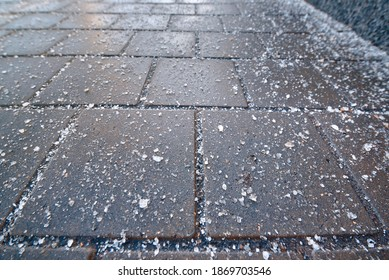 Rock salt crystal sprinkled on paving slabs to avoid slippery surface. Spreading rock salt, keeping sidewalks slip-free all season long. Spread de-icing reagents on sidewalk for melting ice and snow