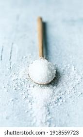 Rock salt on a wooden spoon. Natural food ingredients
